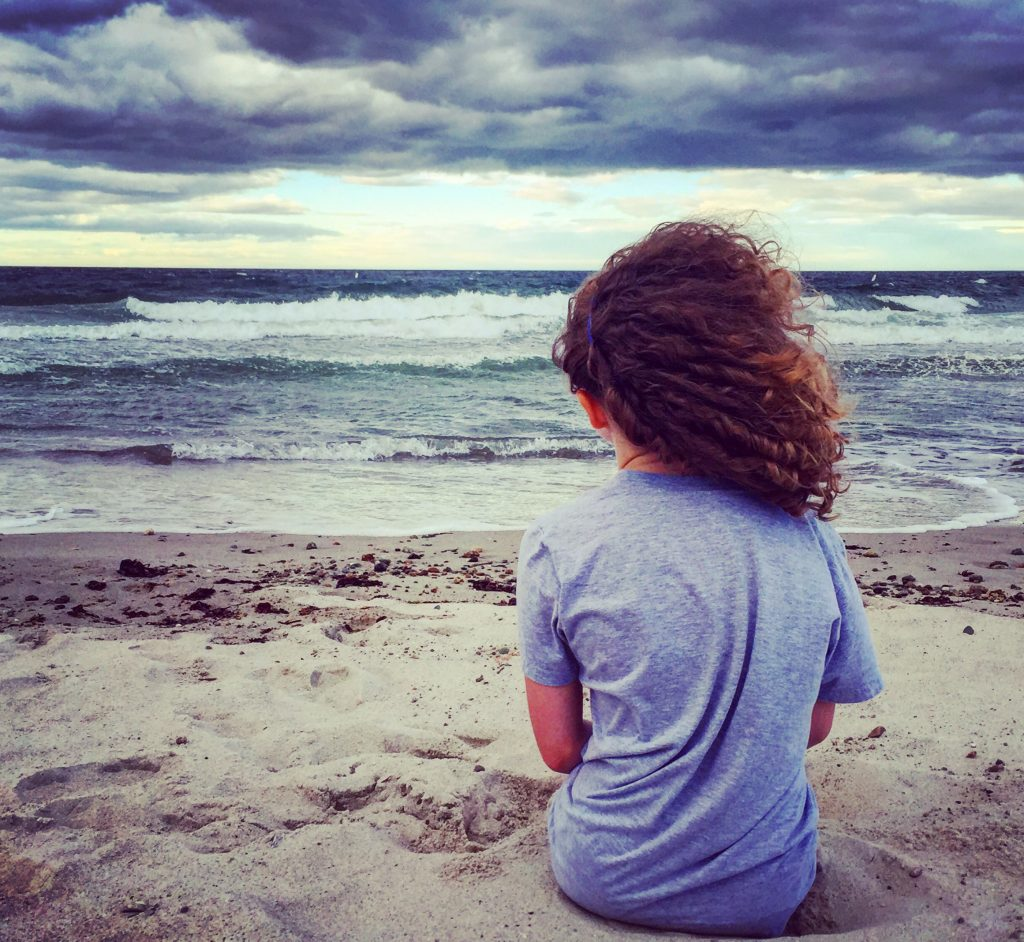 little girl with curly hair sitting in the sand facing the ocean