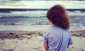 Madilyn, a little girl with curly hair, sits in the sand facing the ocean